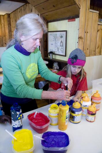 woman teaches young girl crafts