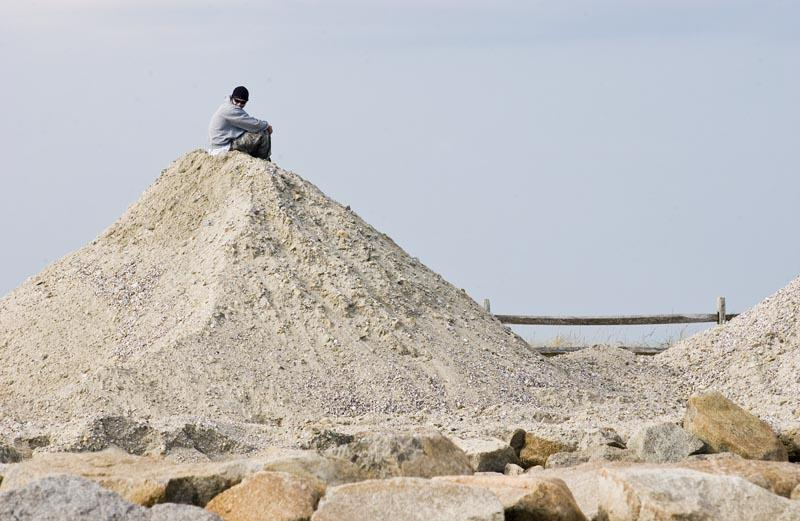 mountain of sand with man sitting on top
