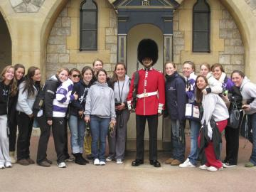 girls lacross team with british guard