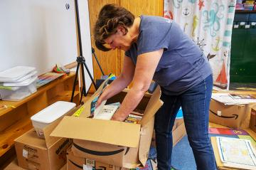 Teacher unpacking boxes in a classroom.